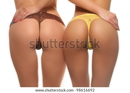 Two sexy female butts in brown and yellow thong