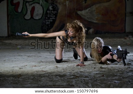 Two sexy female spies in leather outfits shooting from their guns - stock photo