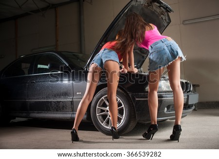 Two sexy girls in high heels examining car engine at auto repair shop. View from the back