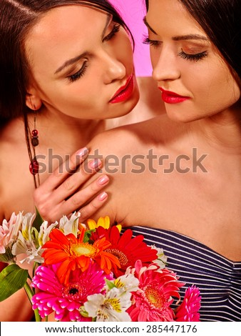 Two sexy lesbian women with flower hugging on pink background.