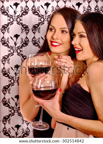 Two sexy lesbian women with red wine. Wallpapers background.