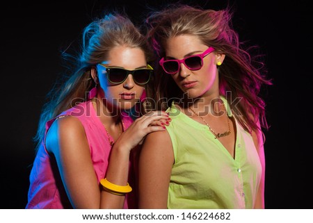 Two sexy retro 80s fashion girls with long blonde hair and sunglasses. Twin sisters together.
