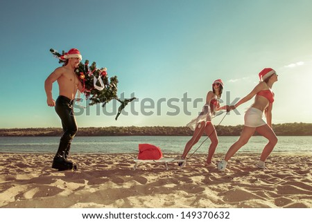 Two Sexy Santos  pulling Santa on a sled with Christmas tree at the beach.  (concept: Tropical winter fun)