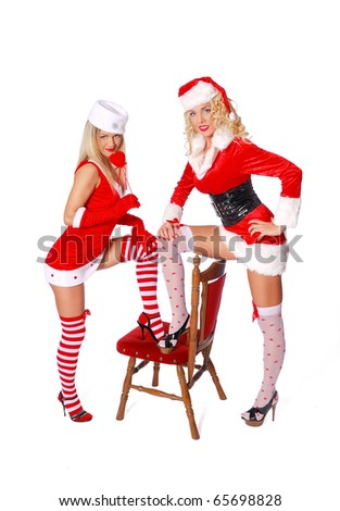 Two sexy woman in red costume put foot on the red chair - stock photo