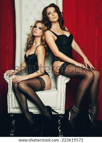 two sexy women in lingerie on white throne. Striptease. - stock photo