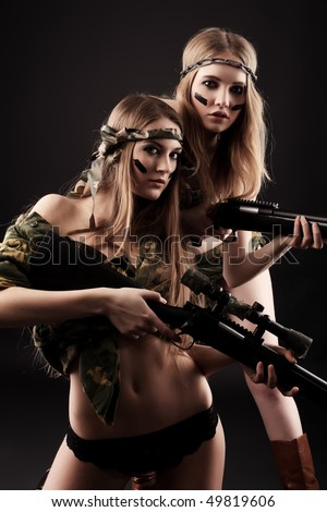 Two sexy women in military uniform posing against black background. - stock photo