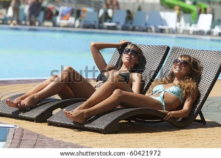 Two sexy young women relaxing on deck chair - stock photo