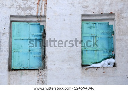 Two shabby windows with green shutters in one of the buildings in the medieval convent in Russia - stock photo