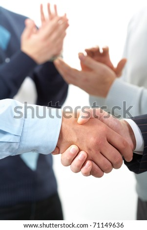 Two shaking hands against applauding hands - stock photo
