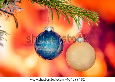 Two shiny xmas baubles on a branch on a tree - stock photo
