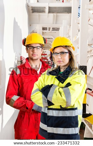 Two ship mates and crew members posing in he ang way on deck of an industrial supply vessel - stock photo