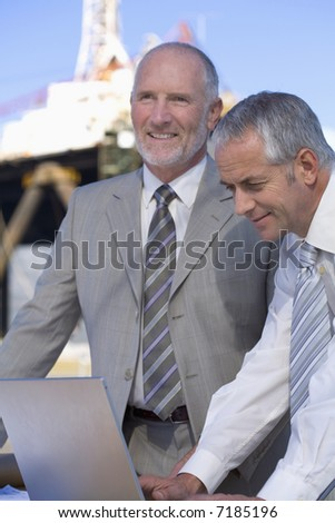 Two shipping businessmen on location in the harbor - stock photo