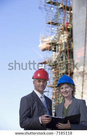 Two shipping engineers in front of an oil platform in the harbor - stock photo