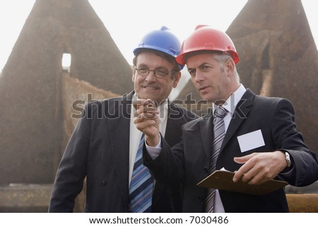 Two shipping inspection engineers taking notes in front of a large rusted anchor in the early morning fog - stock photo