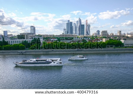 Two ships sail on river at summer day in Moscow, Russia, Skyscrapers far away - stock photo