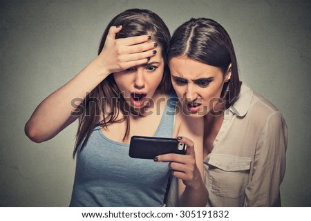 Two shocked women displeased young girls looking at mobile phone seeing bad news message or photos with disgusting emotion on face isolated on gray wall background. Human emotion, reaction, expression - stock photo