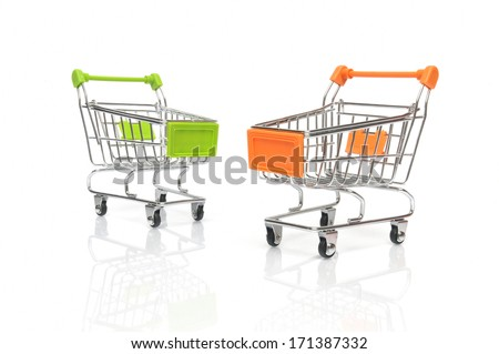 Two shopping carts on white background with reflections  - stock photo