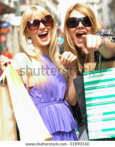 Two shopping woman laughing  in city environment.