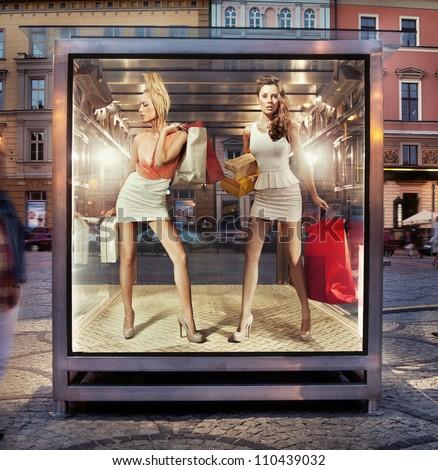 Two shopping women on exhibition window - stock photo