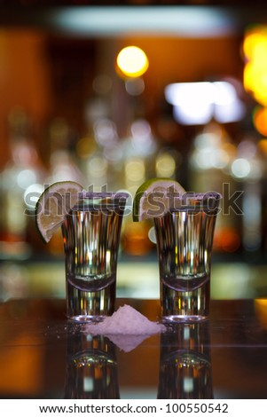 two shots of tequila with lime and salt on a dark wooden table in the background of light bar - stock photo