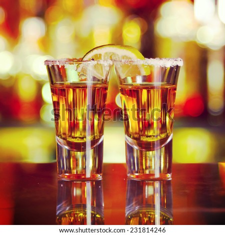 two shots of tequila with lime and salt on the background of the bar - stock photo