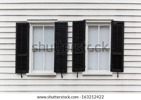 Two shut windows with open blinds on a wooden house - stock photo