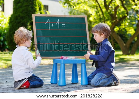 Two  sibling boys at blackboard practicing mathematics, outdoor school or nursery. Back to school concept. - stock photo
