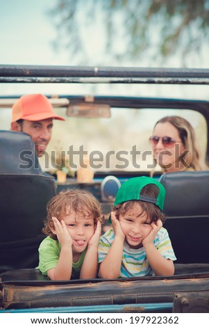Two siblings pulling faces on the back seat of the off-road car - stock photo