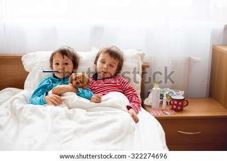 Two sick boys, brothers, lying down in bed with fever, holding teddy bear and resting - stock photo