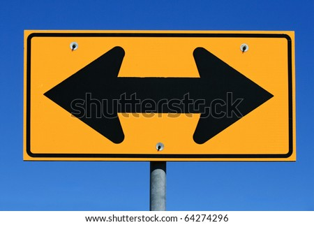 two sided black and yellow road sign designating two way traffic with a blue sky background