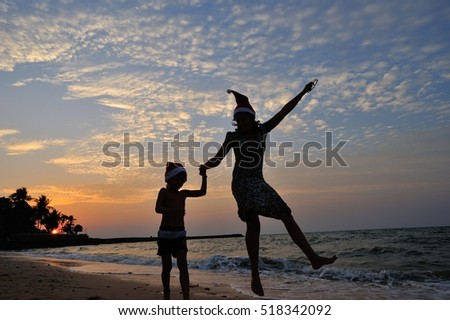 Two silhouettes on the beach with a background of a beautiful sunset: mom and his five year old son are jumping high. On the heads of both is Santaâ??s funny cap.