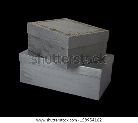 two silver decorated boxes isolated on black