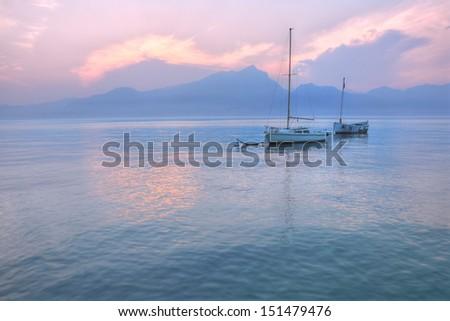 Two single boats at twilight from Lake Garda. - stock photo
