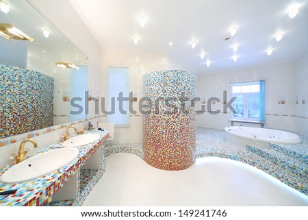 Two sinks and big mirror in spacious bathroom with jacuzzi and blue and red tiles. - stock photo