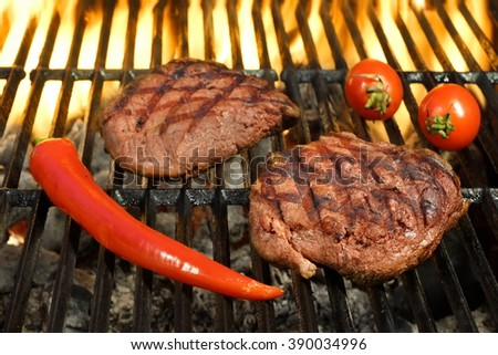 Two Sirloin Beef Steak, Tomato And Chili Pepper On The Hot Flaming BBQ Grill, Close Up, Top View - stock photo