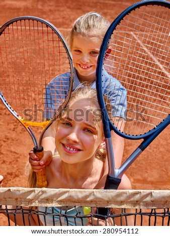 Two sister girl athlete  with racket and ball on  brown tennis court. - stock photo