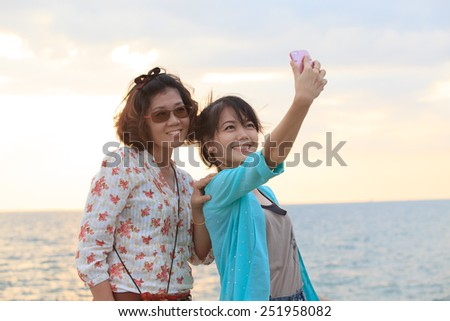 two sister take a photo,selfie by smart phone beside sea beach with happy emotion - stock photo