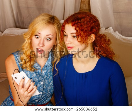 Two sisters, a blonde and a redhead, listening to music on headphones. Girl surprise looks at the phone screen, defeated the last news in social networks. Sisters sitting in the bedroom. - stock photo