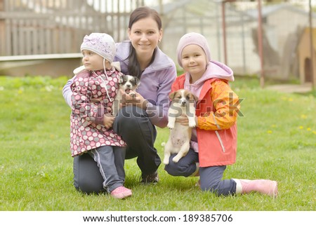 Two sisters and mother playing with puppies  - stock photo