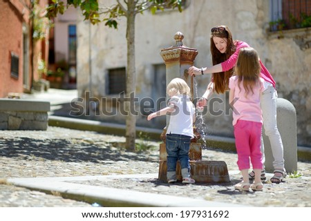 Two sisters and their mother having fun with drinking water fountain in Italy - stock photo