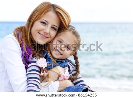 Two sisters 5 and 22 years old at the beach in sunny autumn day. - stock photo