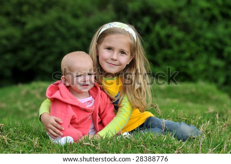 Two sisters are sitting on the lawn - stock photo