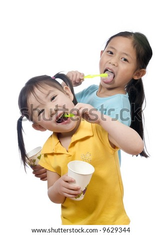 Two sisters brushing thier teeth. Health and living. - stock photo