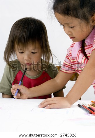 Two sisters draw a picture together. Sharing, siblings, help, teaching