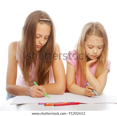 Two sisters draw on the album. Isolated on white background - stock photo