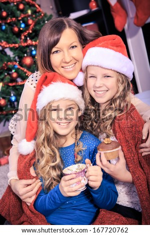 two sisters drinking tea with xmas cookies at home - stock photo