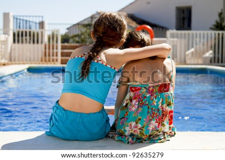 Two sisters embracing each other by the pools edge - stock photo