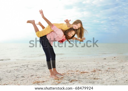 Two sisters enjoy summer day at the beach. - stock photo