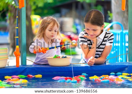 Two sisters, fishing in the paddling pool - stock photo