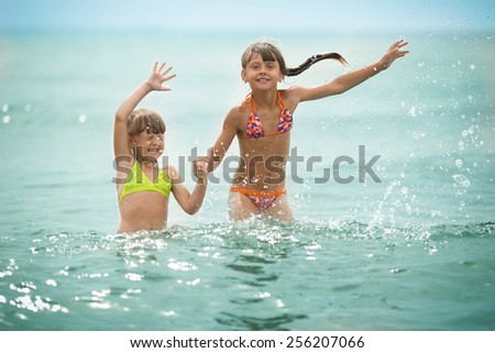 two sisters happily basking in the summer sea - stock photo